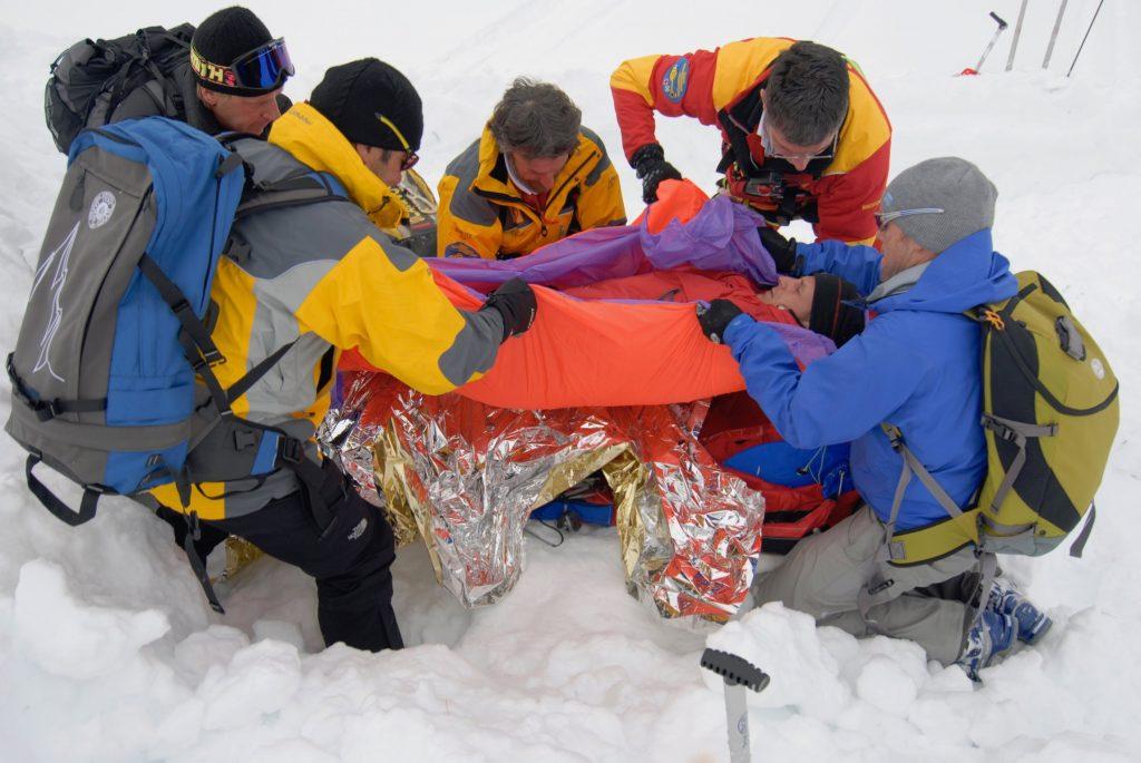 Nicht nur für Pausen, (Not-)Biwaks und zum Wärmeerhalt nach Unfällen ist ein Biwaksack gut. Auch für einen kurzenTransport bzw. wie im Foto zum schionenden Umlagern in die Vakuummatratze der Flugrettung kann er hervorragende Dienste leisten. I bergundsteigen.blog