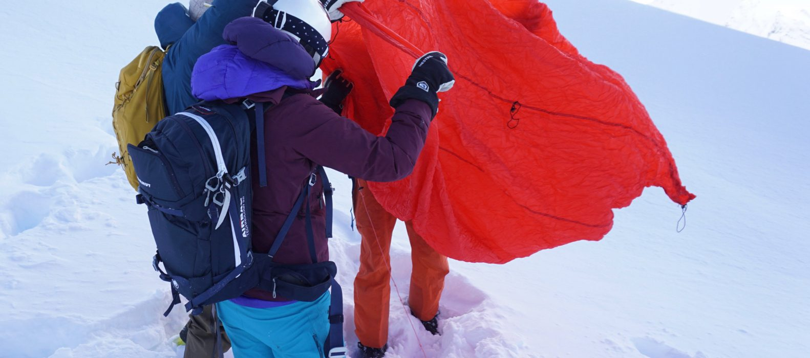 """HILLEBERG """"Windsack"""", Abb. 2: Beim Ausbreiten sieht man gleich die Befestigungspunkte/-schnüre sowie die lange Sicherungsleine (liegt im Schnee), die man vor dem Auspacken am Handgelenk/Körper fixieren kann, damit der Wind das ganze Ding nicht wegbläst."""