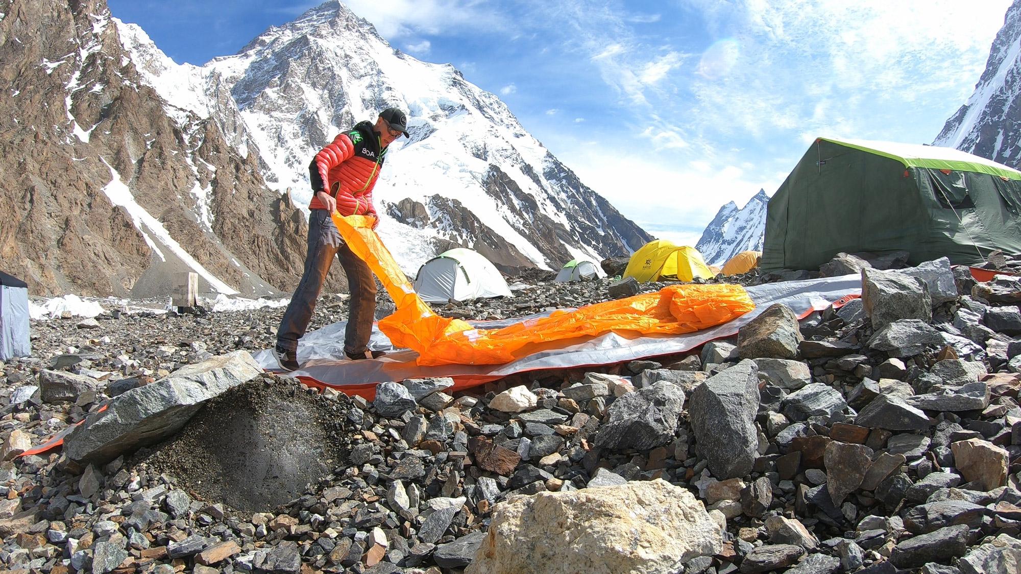 Max Berger mit Schirm am Fuß des K2 I bergundsteigen.blog