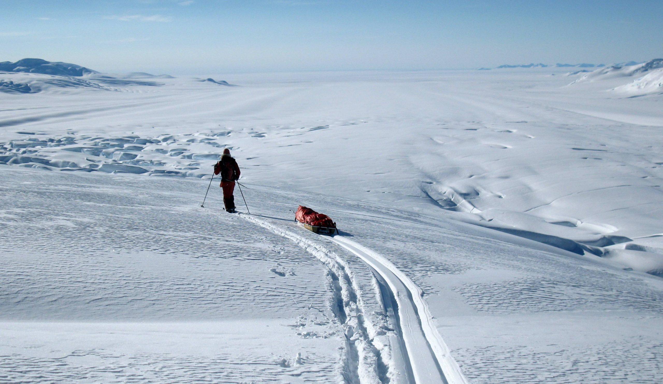 Cecile Skog (NOR) sucht eine sichere Abstiegsroute vom Südpolarplateau über den spaltenreichen Axel Heiberg Gletscher hinunter zur inneren Küstenlinie, wo das Ross-Schelfeis (in Bildmitte hinten) beginnt. Foto: Ryan Waters 2010