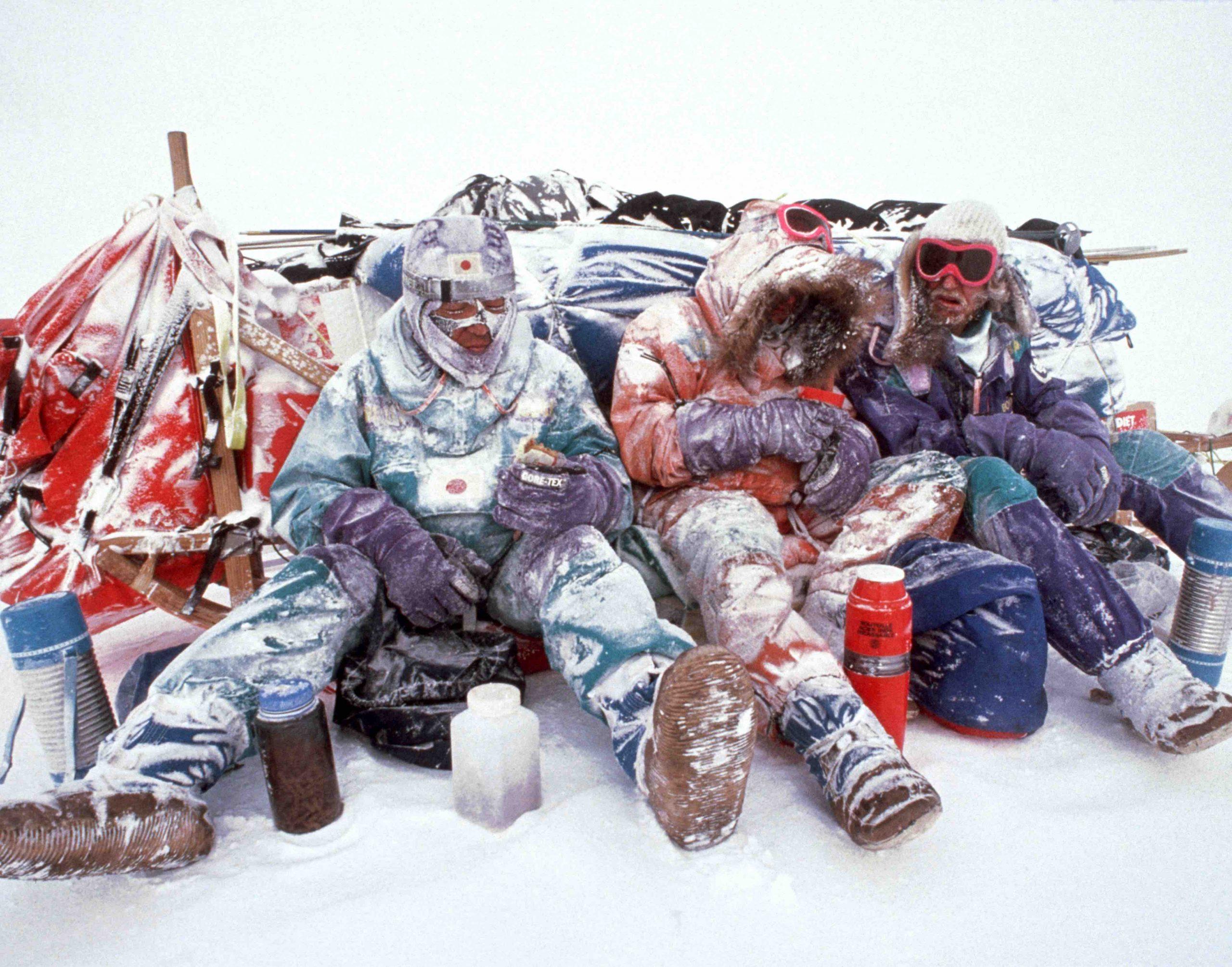 Abb. 5 Wind, Eis und Kälte bei einer Pause der Transantarctica 1989/90 scheinen Keizo Funatsu (JP), Jean-Louis Etienne (F) und Victor Bojarski (USSR) im Windschatten ihres Hundeschlittens nichts anhaben zu können. Die Transantarctica ist mit 6.048 Kilometern von der Antarktischen Halbinsel über den Südpol bis an die Küste der Ostantarktis in 220 Tagen die längste jemals durchgeführte Durchquerung des antarktischen Kontinents. Foto: Will Steger 1990