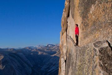 """""""To honnold"""": Honnold balanciert auf dem Thank God Ledge in der Regular-Northwest-Route am Half Dome im Yosemite Valley – 600 Meter über dem Talboden. Später schrieb er: """"Das Thank God Ledge mit dem Rücken zur Wand entlang zu spazieren, ist erstaunlich gruselig."""" Foto: Jimmy Chin"""